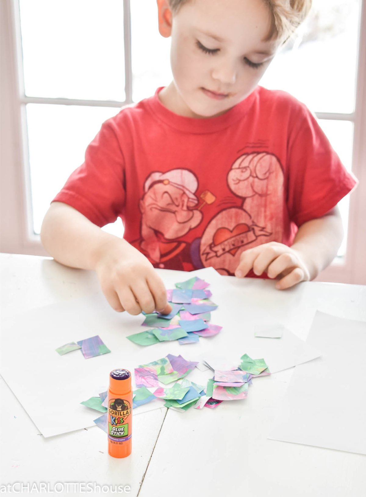 Young boy using Gorilla Glue Stick with small pieces of paper