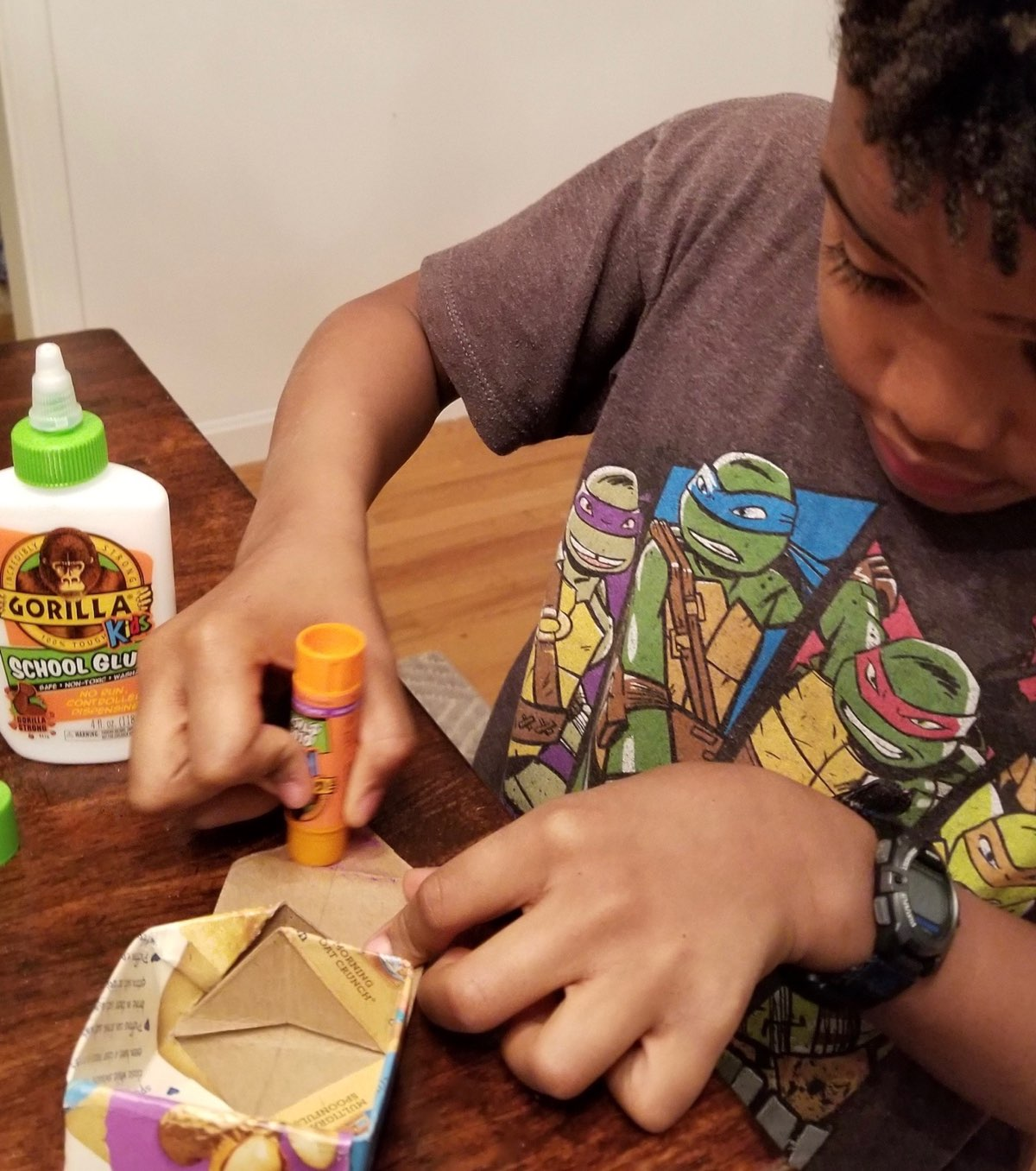 Young boy using Gorilla Glue Stick on cardboard